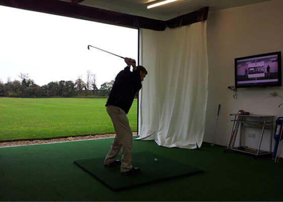 Golfer driving in an outdoor academy