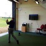 Golfer hitting out from inside the teaching bay